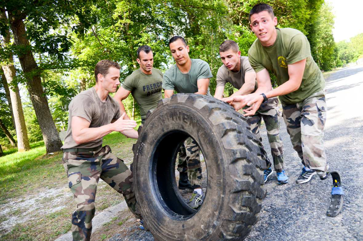 Cinq militaires poussent un gros pneu. Un des militaires porte un pied prothétique.