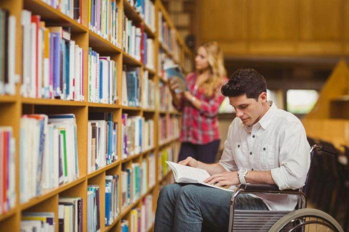 Un homme en fauteuil roulant consulte un document dans une bibliothèque universitaire.
